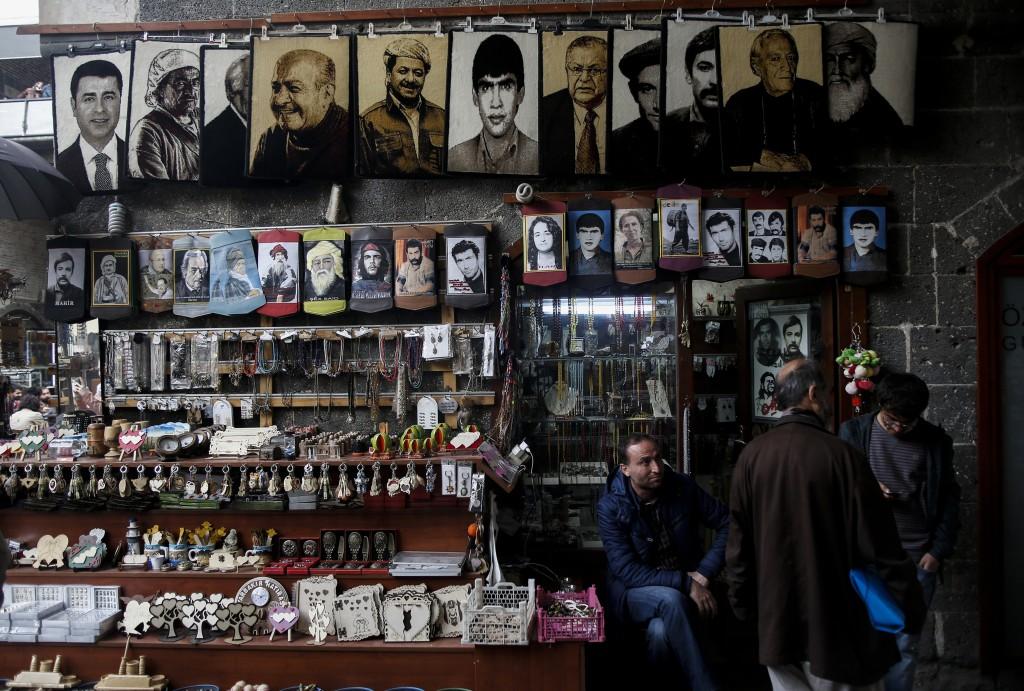 Dans le quartier historique de Sur dans la province de Diyarbakir. Sous couvre-feu pendant des semaines, le quartier est aujourd'hui en ruines. Cette échoppe de souvenirs dans le Hasan Paşa Han expose des photos de nombreux leaders politiques, acteurs, poètes, chercheurs, figures de proue du mouvement politique et artistique kurde ainsi que de la guérilla kurde, et des figures de la gauche marxiste turque. Nombre de ces représentants ont été exilés et/ou assassinés, leurs travaux ont été interdits et il était interdit d'écouter leurs musiques, de regarder leurs films ou de parler de leur histoire. En commençant en haut à gauche, Selahattin Demirtaş, co-leader actuel du parti HDP. Melle Mustafa Barzani, fondateur du PDK, les pesmerge kurdistan d'Irak, symbole de rébellion chez les Kurdes. Mesut Barzani, président actuel du gouvernement régional kurde en Irak. Mazlum Doğan, l'un des fondateurs du PKK, il s'était immolé dans la prison de Diyarbakir le 21 mars 1983 (Newroz, fête de nouvelle année). Celal Talabani, fondateur du parti YNK au Kurdistan d'Irak, ancien président de l'Iraq. Şeyh Sait, symbole de la deuxième révolte kurde en 1927, Diyarbakir. Seyid Riza, symbole de la troisième résistance kurde-Alévi de Dersim. Ahmed Arif et Cigerxwîn sont tous deux des poètes très connus. Musa Anter, Ape Musa, un représentant de l'intelligentia kurde assassiné à Diyarbakir en 1992. Yilmaz Guney, cinéaste, et Ahmet Kaya, chanteur, tous deux exilés en France. Sakine Cansiz l'une des fondatrices du PKK et du mouvement des femmes kurdes, assassinée à Paris en 2013.