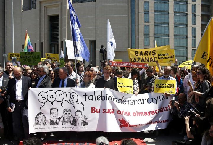 """Le 22 avril 2016, devant le Palais de justice à  Çağlayan à Istanbul. Jour du procès des deux journalistes de Cumhuriyet Can Dundar et Erdem Gül (qui tiennent la banderole à gauche) ainsi que des quatre universitaires emprisonnés depuis le 15 mars 2016.  Esra Mungan, Meral Camci, Muzaffer Kaya et Kivanç Ersoyont ont été emprisonnés pour avoir lu une déclaration de presse qui répète notre exigence de paix tout en soulignant les pressions et menaces subies par les universitaires depuis début janvier. Tous seront mis en liberté provisoire alors que leurs procès continuent sans chef d'accusation clair.   Sur la banderole et au dessus des portraits des quatre universitaires : """"Nous insistons pour la paix"""", """"On ne peut pas incarcérer la paix"""" """"La paix va gagner"""", """"Nous ne serons pas complices de crime !"""" Photo Ulaş Yunus Tosun"""