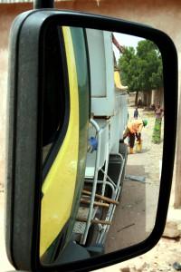 Dans le rétroviseur du camion benne, des éboueurs Hysacam ramassent la poubelle d'une ménagère de Garoua dans le cadre de la collecte porte-a-porte, novembre 2010, photo E. Guitard