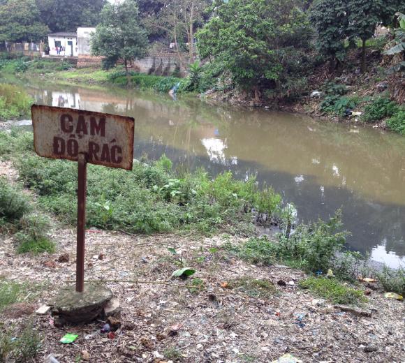 Ici, l'eau noire des usines ne se mélange pas avec l'eau brune de la rivière. Cấm Đổ Rác : « dépôt de déchets interdit » — 26 mars 2014, MLM