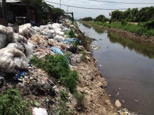 Les déchets plastiques à recycler s'amoncellent sur chaque espace disponible, comme ici, sur la rive du canal artificiel traversant la commune de Nhu Quynh — 20 juin 2014, MLM